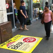 Bright Yellow Beer ad showing 20% off on the sidewalk done with Zig Posterman Whole Foods New York City Gets Attention Sidewalk Paint Markers!