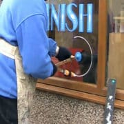 Removing Chalk Window Art, sign painter using a homemade compass to make a sign in a window. Circle is half done, with nice blue text above