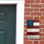 Slate art board with rustic Americana 18-star flag painted with chalk markers, hanging on brick wall next to wooden door