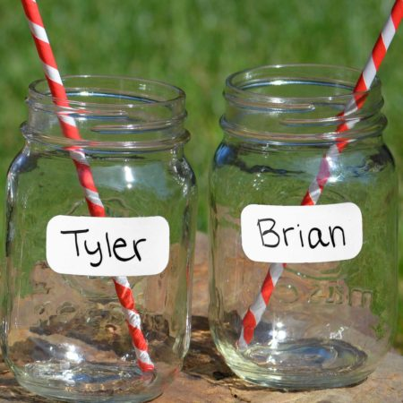 "Two mason jars with white party labels applied to each, with the names ""Tyler"" and ""Brian"" written out. Sitting on a rock, with red and white striped straws in each jar."
