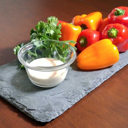 Peppers and dip displayed on a piece of skinny slate.