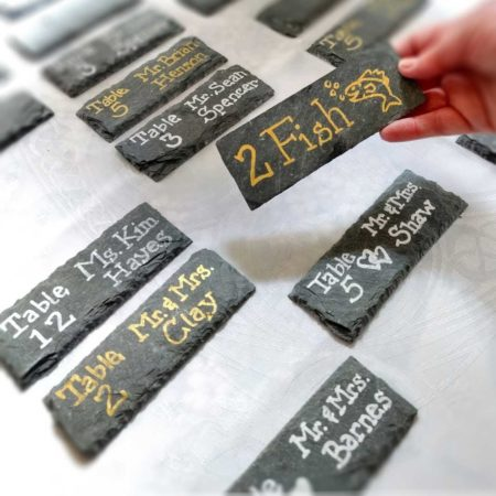 """Set of slate wedding and event place cards on a white table cloth, each with names and table assignments written out. A hand hold one to show the backside, where the words """"2 Fish"""" and an image of a fish appear."""