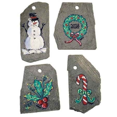 Hand Painted Slate Christmas Ornaments on a white background featuring a snowman, wreath, holly berry, and candy cane